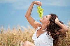 Mujer que come las uvas en campo de trigo. Comida campestre. Imagen de archivo