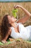 Mujer que come las uvas en campo de trigo. Comida campestre. Foto de archivo
