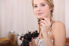 Mujer que come las uvas rojas Fotografía de archivo