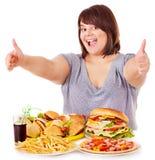 Mujer que come los alimentos de preparación rápida. fotografía de archivo libre de regalías