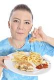 Mujer que come los alimentos de preparación rápida imagen de archivo