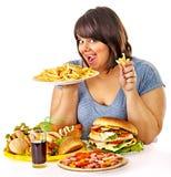 Mujer que come los alimentos de preparación rápida. Imagen de archivo