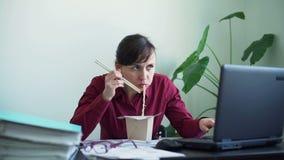 Mujer que come los alimentos de preparación rápida mientras que trabaja en oficina almacen de video