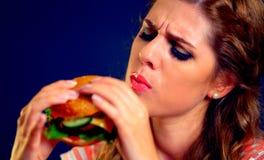 Mujer que come los alimentos de preparación rápida Muchacha que goza de la hamburguesa deliciosa Fotografía de archivo libre de regalías