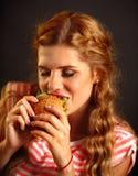 Mujer que come los alimentos de preparación rápida Muchacha que goza de la hamburguesa deliciosa Imagenes de archivo