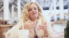 Mujer que come los alimentos de preparación rápida y la risa del pollo almacen de video