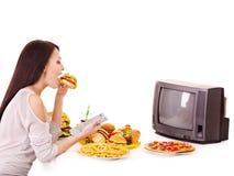 Mujer que come los alimentos de preparación rápida y que ve la TV. Imagen de archivo