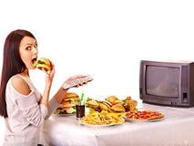 Mujer que come los alimentos de preparación rápida y que ve la TV. Foto de archivo libre de regalías