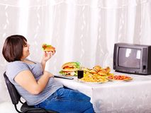 Mujer que come los alimentos de preparación rápida y que ve la TV. Imagen de archivo libre de regalías