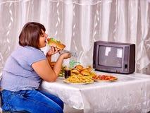 Mujer que come los alimentos de preparación rápida y que ve la TV Fotos de archivo