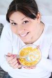 Mujer que come los cereales de los copos de maíz Foto de archivo libre de regalías