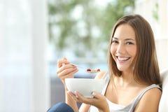 Mujer que come los copos de maíz en casa Imagen de archivo libre de regalías
