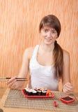 Mujer que come los rodillos de sushi Fotos de archivo