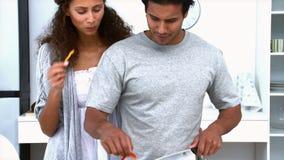Mujer que come mientras que su marido está cocinando verduras almacen de video