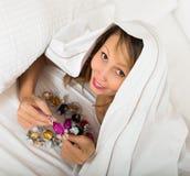 Mujer que come secretamente el caramelo en cama Fotografía de archivo