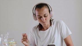 Mujer que come su música que escucha del cereal en auriculares y smartphone de la ojeada metrajes