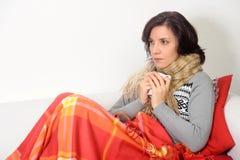 Mujer que come té de consumición frío de la garganta dolorida imagenes de archivo