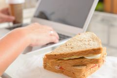 Mujer que come un bocadillo del desayuno mientras que trabaja con un ordenador portátil fotos de archivo