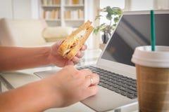Mujer que come un bocadillo del desayuno mientras que trabaja con un ordenador portátil foto de archivo libre de regalías