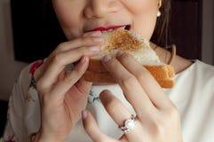 Mujer que come un emparedado Fotografía de archivo libre de regalías