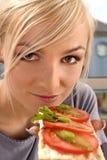 Mujer que come un emparedado del tomate Imagen de archivo