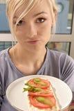 Mujer que come un emparedado del tomate Foto de archivo