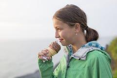 Mujer que come un helado delicioso en la puesta del sol Imagenes de archivo