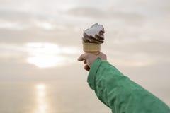 Mujer que come un helado delicioso en la puesta del sol Foto de archivo libre de regalías