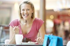 Mujer que come un pedazo de torta en la alameda fotos de archivo