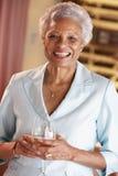 Mujer que come un vidrio de vino en una barra imagenes de archivo