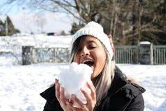 Mujer que come una bola de la nieve Padre y niño que juegan junto Ropa del invierno foto de archivo