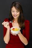 Mujer que come una ensalada de fruta Fotos de archivo libres de regalías