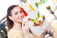 Mujer que come una fresa y un postre del helado Imagen de archivo libre de regalías