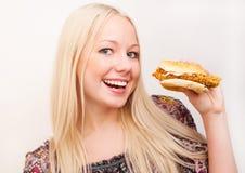 Mujer que come una hamburguesa Fotografía de archivo