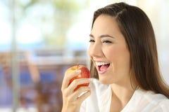 Mujer que come una manzana en casa Fotos de archivo