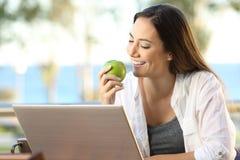 Mujer que come una manzana usando un ordenador portátil Fotos de archivo