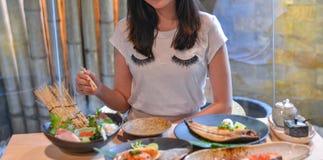 Mujer que come y que disfruta de la comida japonesa foto de archivo libre de regalías