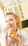 Mujer que come zanahorias Imagenes de archivo