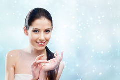 Mujer que comienza a aplicar la crema protectora del invierno Imagenes de archivo
