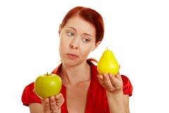 Mujer que compara la manzana y la pera Foto de archivo