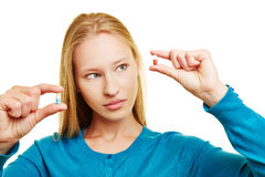 Mujer que compara píldoras en sus manos Foto de archivo libre de regalías