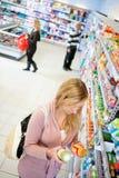 Mujer que compara precios imagen de archivo libre de regalías