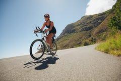 Mujer que compite en la pierna de ciclo de un triathlon Fotografía de archivo libre de regalías