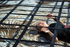 Mujer que compite y que lucha en fango en carrera de obstáculos Fotos de archivo libres de regalías