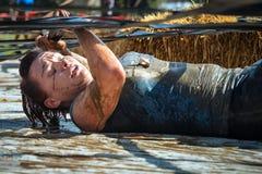 Mujer que compite y que lucha en fango en carrera de obstáculos Imagenes de archivo