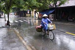 Mujer que completa un ciclo en un día lluvioso en hoi un Vietnam fotografía de archivo libre de regalías