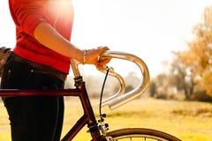 Mujer que completa un ciclo en la bicicleta en parque del otoño Imagen de archivo libre de regalías