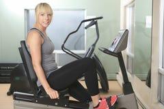 Mujer que completa un ciclo en la bicicleta estática en gimnasio Fotografía de archivo libre de regalías