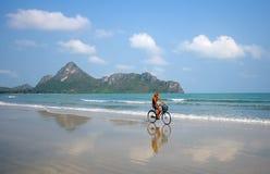Mujer que completa un ciclo en la playa imagen de archivo