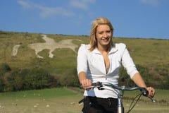 Mujer que completa un ciclo en un campo. Imagen de archivo libre de regalías